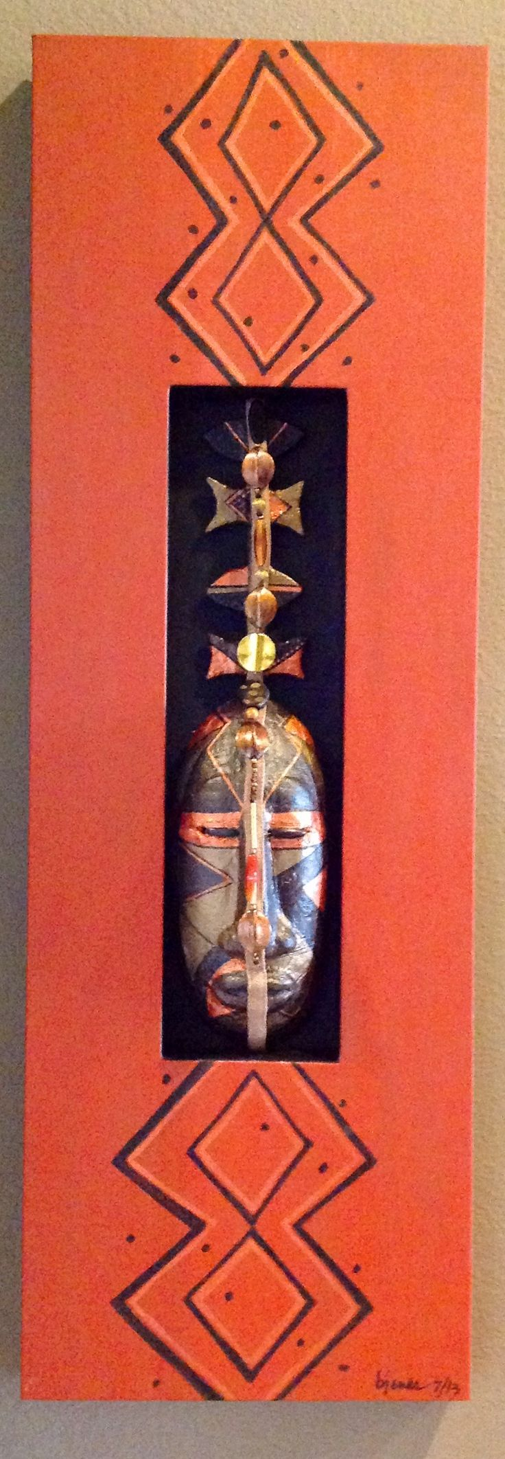 Shadow box canvas with inset sculpted Congo mask accented with metallic paint and beads.