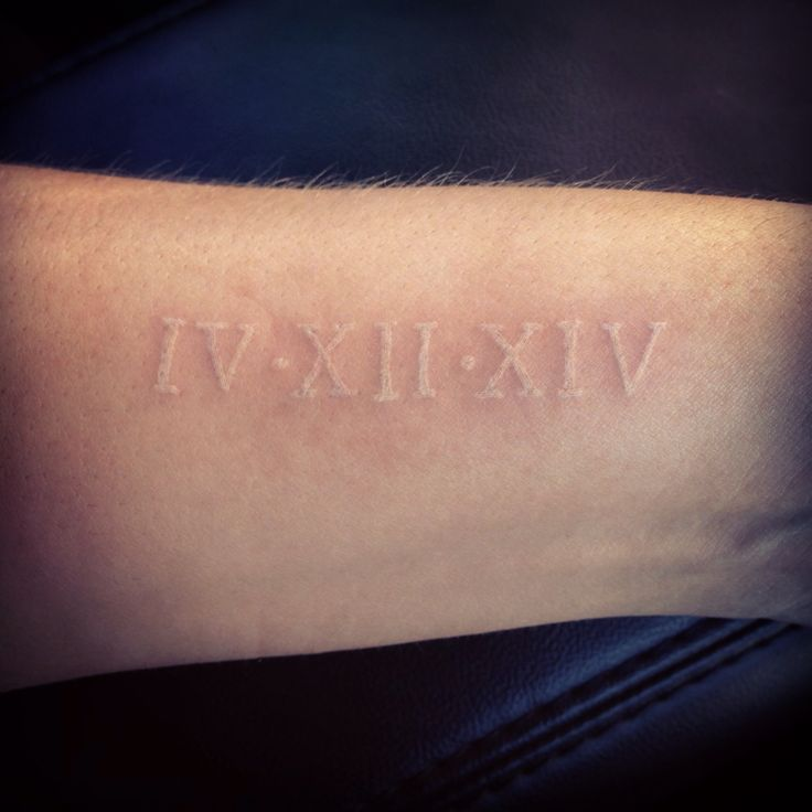 Roman numeral wedding date tattoo in white