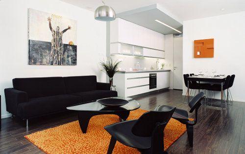 living. paredes blancas, muebles negros y tono de acento naranja