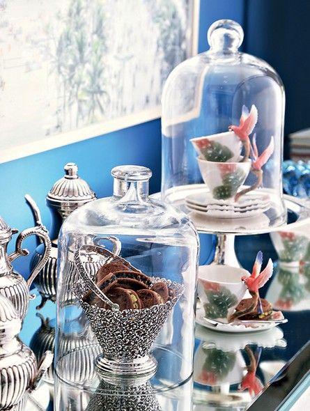 Na mesa do café, as xícaras chinesas com araras nas asas, arrematadas em leilão da coleção de Bethy Lagardère, ganham status de arte sob redomas de vidro. Na cesta de prata, biscoitinhos