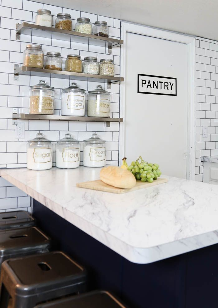 Can't believe these gorgeous white countertops are laminate and look like marble at a fraction of the cost. Those jars and shelves are amazing! - www.classyclutter.net