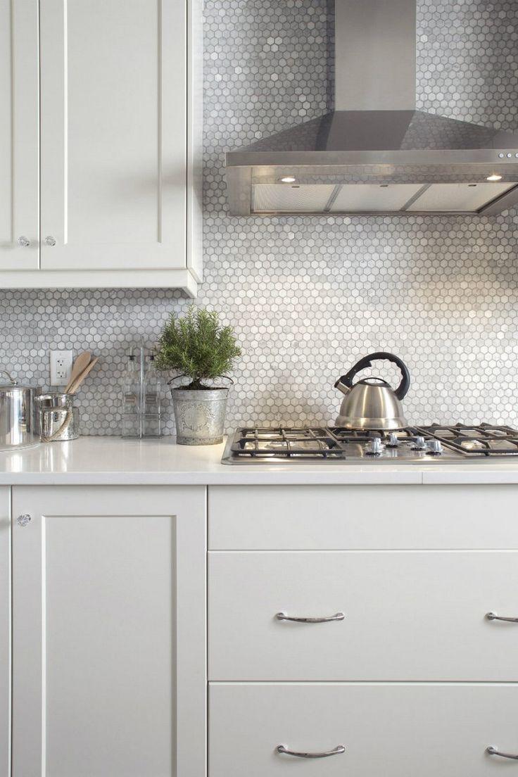 crédence cuisine en tomettes hexagonales en gris clair, hotte en acier inox et…