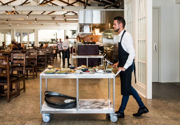 A beautiful, sunlit mezzanine serving antipasti from marble carts.