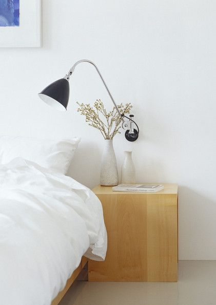 This wooden cube sits under a wall-mounted lamp for maximum impact in a minimalist room.