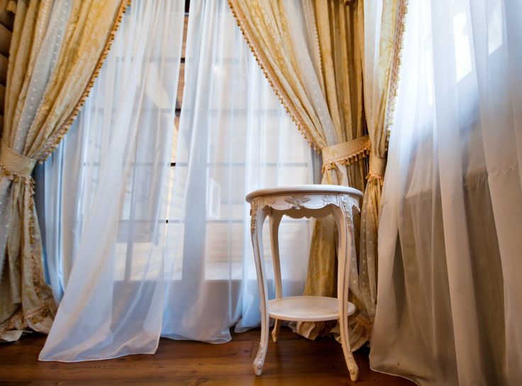 It will have beautiful grey draped curtains and thin material covering the window, like the picture.