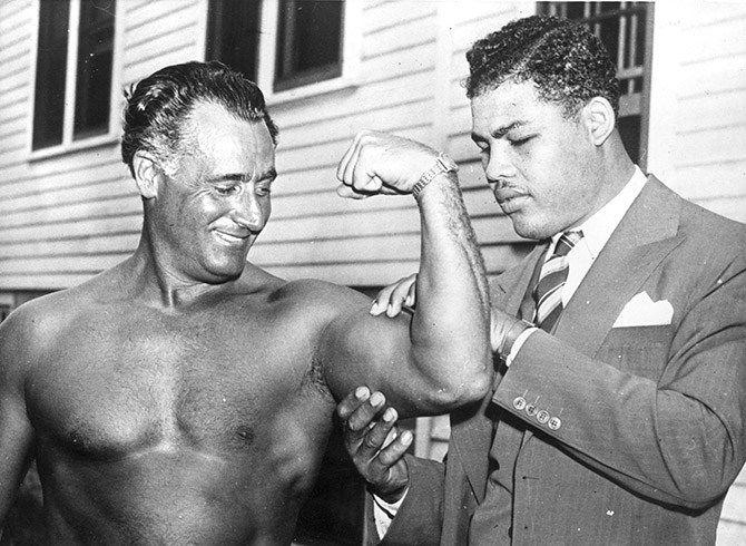 Чемпион мира в супертяжелом весе по боксу Джо Луис восхищается бицепсу Чарли Атласа (Charles Atlas), который считался на то время самым накачанным человеком в мире, 1938 год