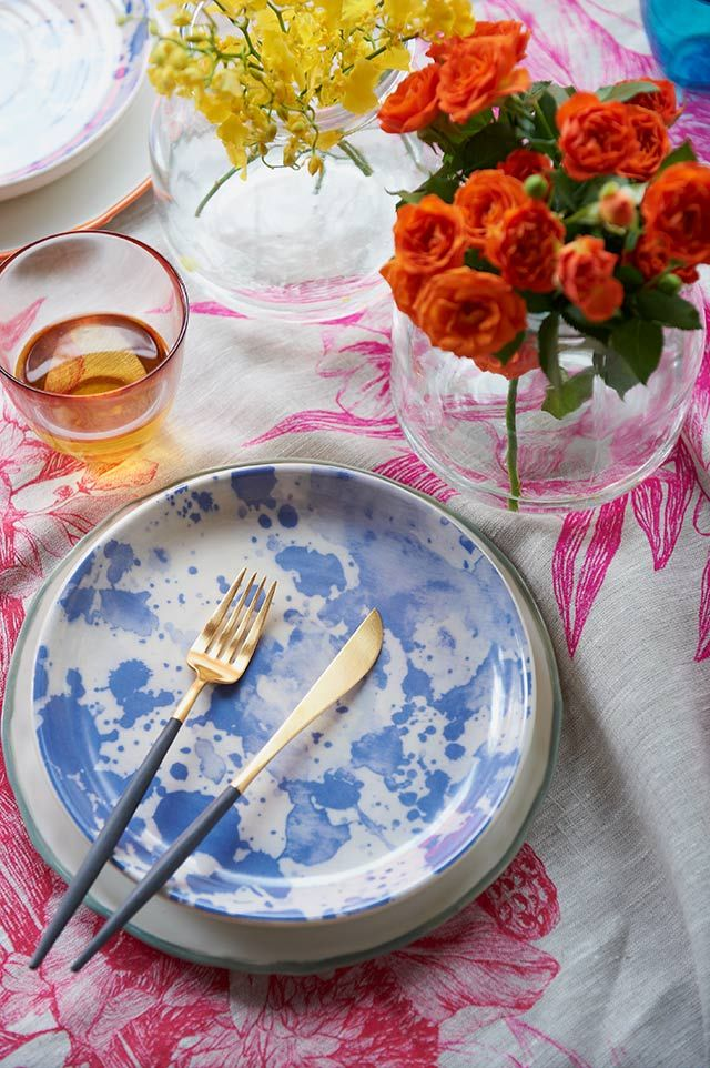 Bonnie and Neil 'Lotus Pink' tablecloth and 'Watercolour' plate in blue.