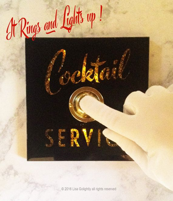 The perfect gift for anyone who appreciates a little cocktail service on occassion ( and who doesnt? ) I have always had a love affair with antique glass signage found in old bars and hotels. This COCKTAIL SERVICE button celebrates such signage from a bygone era. Reverse printed beveled glass has a shadow box effect with a gold glitter background. This piece not only rings but lights from within when the antiqued brass button is pressed. Our buttons have been featured in Veranda, Elle Decor…