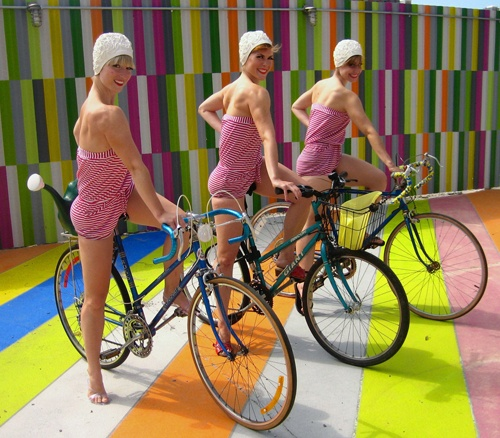 Girls on bikes, in Brooklyn, with stripes and swimming caps.  Like synchro swimmers who're totally over the water!  Yeah!