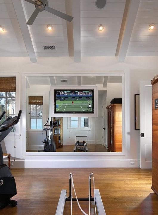 Home gym with TV mounted on mirrored wall