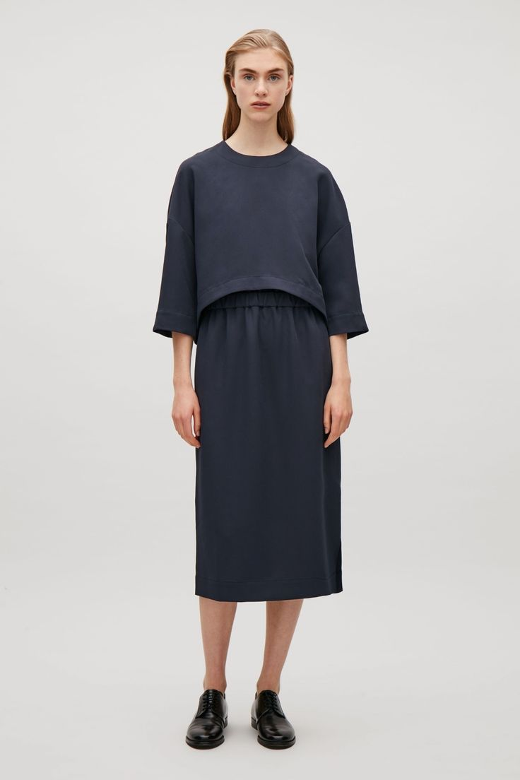 A sleeveless dress under a rounded ¾ sleeve top, this layered design is made from a twill fabric with a tactile finish. Coming in at the waist with elastic detail, it has simple round neckline, subtle in-seam pockets and a hidden zip and hook fastening at the back.