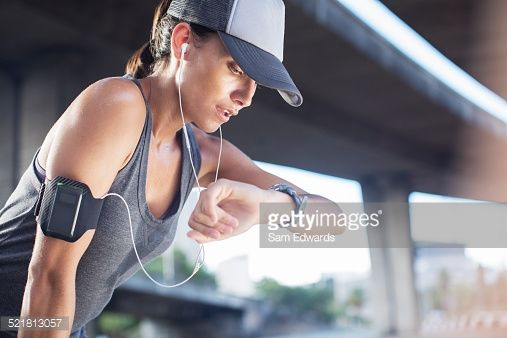 Stock Photo : Woman looking at watch after exercising on city street