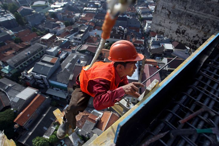 A worker steps on scaffolding with a life rope at an apartment construction site in Jakarta, Indonesia, on Aug. 27 | © Tatan Syuflana | Associated Press