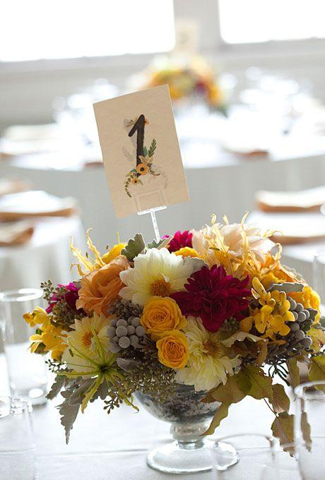 Brides.com: Fall Wedding Centerpieces. Wedding centerpiece of dahlias, garden roses, vanda orchids, silver brunia, gloriosa lilies, dusty miller, pear foliage, and seeded eucalyptus by QuatreCoeur Browse more classic wedding centerpieces.