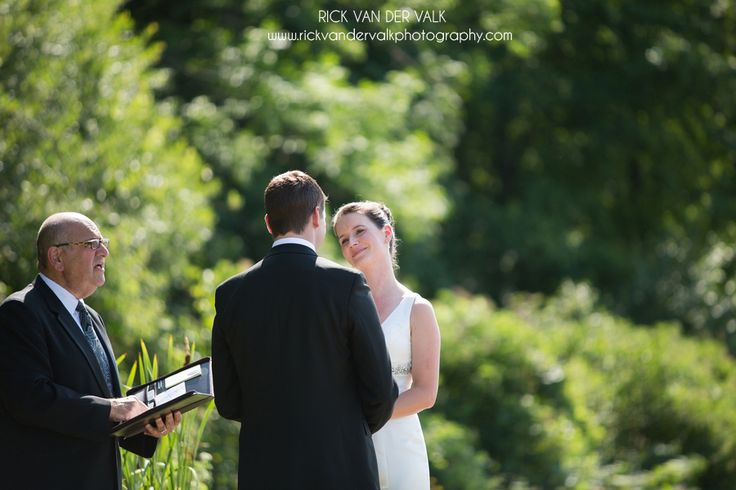 Couple taking vows during sunny summer wedding at Cave Spring Winery.