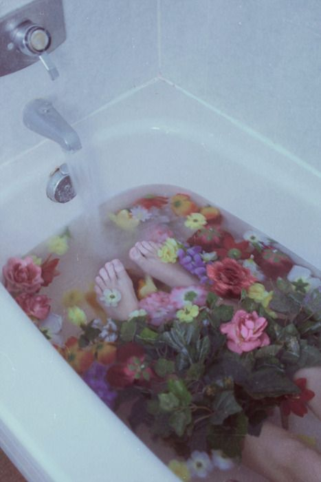 nostalgic, dreamy, girl lays in filling bathtub with many colored roses and flowers, lomography, water