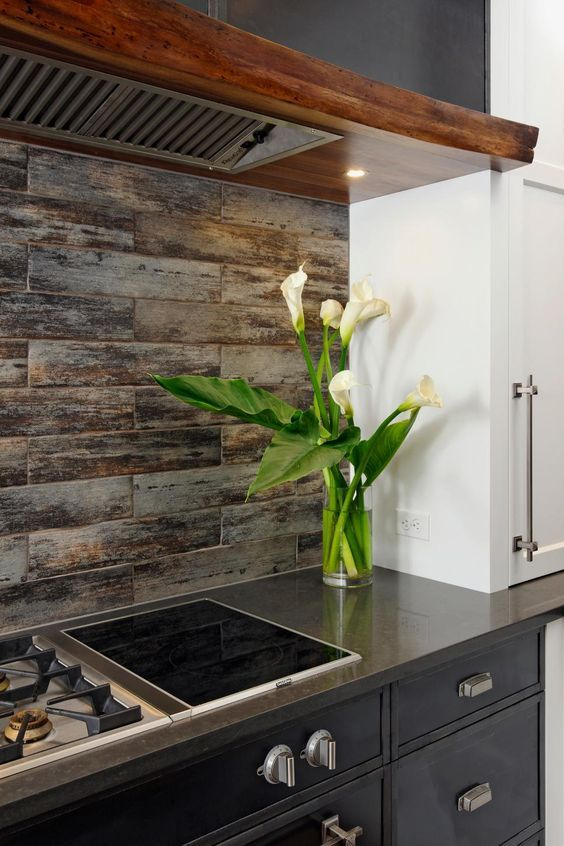 Ceramic tile mimics the look of weathered wood, creating a backsplash that perfectly complements this modern kitchen's rustic-industrial vibe. Hot-rolled steel panels form the cabinetry that surrounds the cooktop, and a custom hood is made from live-edge walnut, warming up the space.