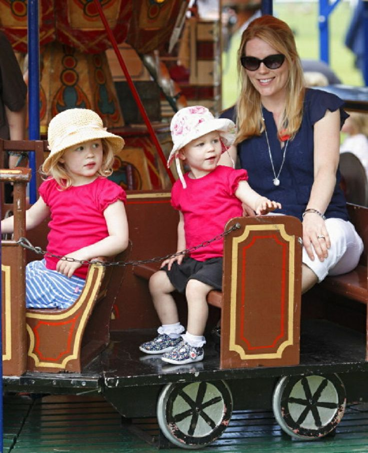 Autumn Phillips and daughters Savannah Phillips (left) and Isla Phillips (center) ride a merry go round during day 4 of the Royal Windsor Horse Show at Home Park, 17.05.4 in Windsor, England