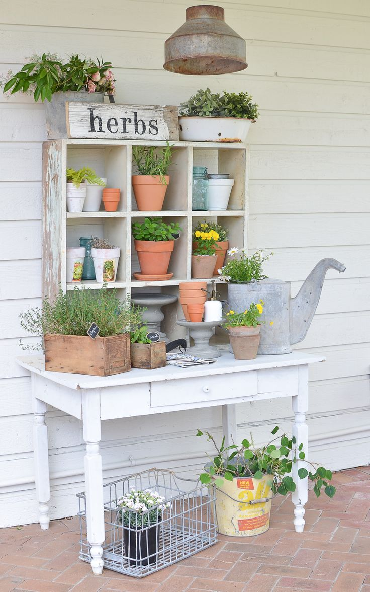 This farmhouse style potting bench is full of vintage charm and perfect for summer. Complete with a chippy white table and vintage cubby.