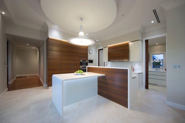 Une cuisine minimaliste en blanc combiné avec des portes en bois