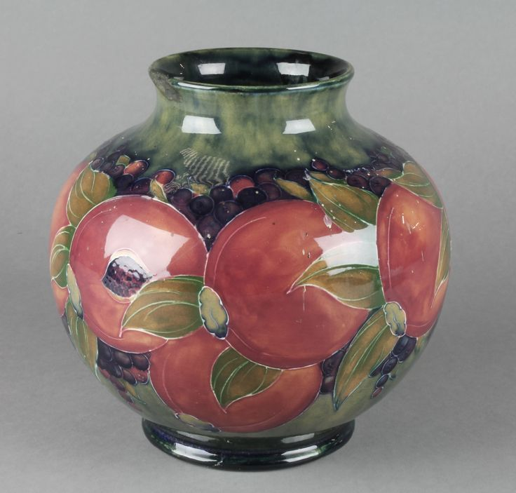 """Lot 2, A Moorcroft baluster vase decorated with pomegranate design on a green ground with impressed and signature marks 7 1/2"""", est £200-400"""