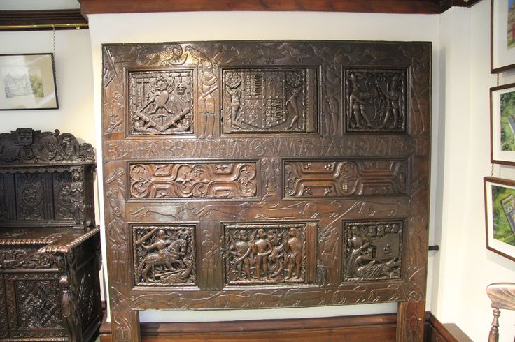 Carved cupboard front, mid 16th century, Welsh, displayed at Cotehele House, Cornwall. Includes religious imagery, various figures, heraldry and an inscription.