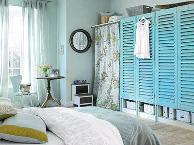 creating closets...tension rods & drapery, simple box store melamine bookcases covered w/reclaimed shutters...top the entire wall w/a wide plank board for display...I love this!