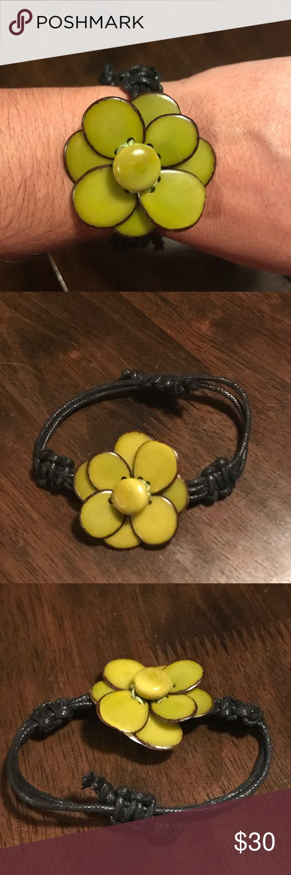 A beautiful handmade Tagua flower bracelet This bracelet is a flower made of various pieces of Tagua which comes from the seed of the tropical palm tree fruit. It is hand picked, carved, colored and designed into a flower and placed on a black leather slip knot bracelet. Jewelry Bracelets