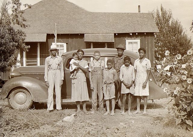 1930s photo of Black family posing in front of their home and car
