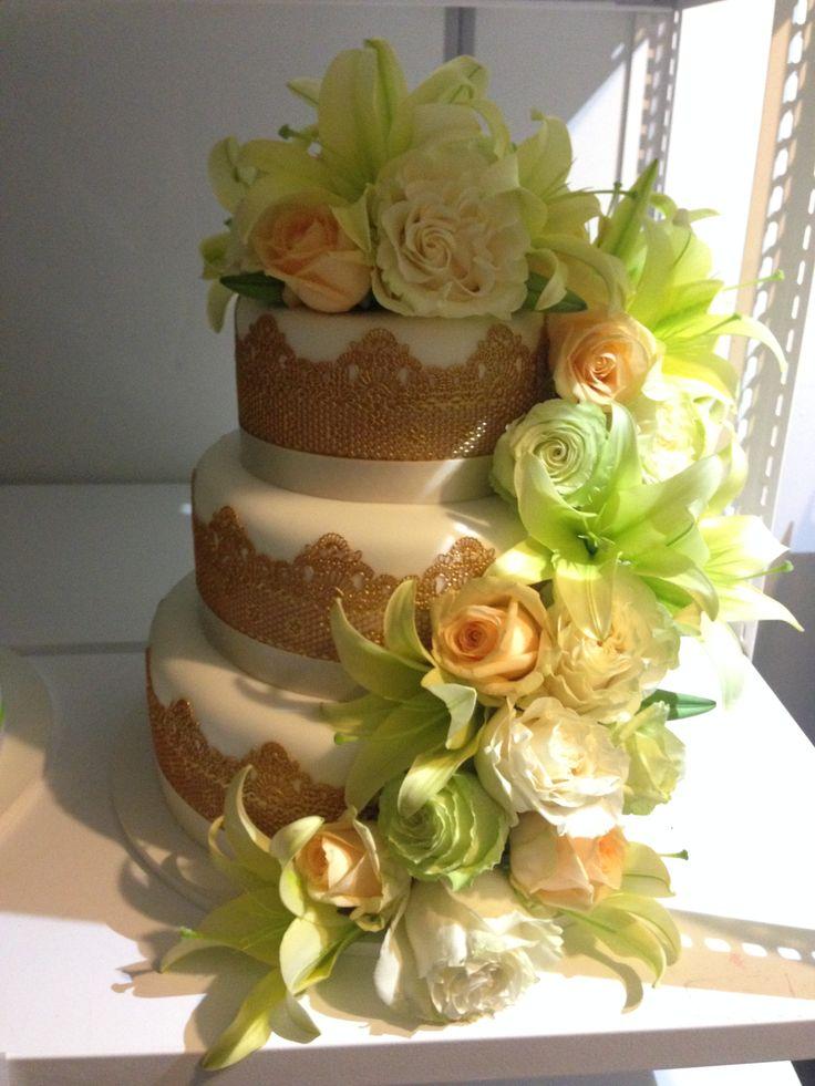 Třípatrový svatební dort potažený fondánem, dozdobený jedlou krajkou a živými květinami.