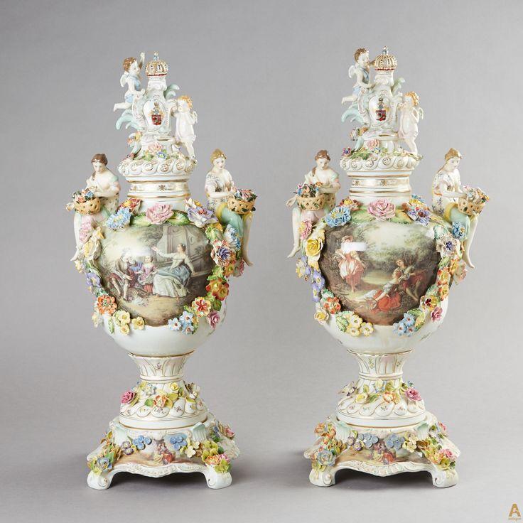 Уникальная пара фарфоровых ваз, богато украшенных элементами декора в виде девушек с корзинками цветов, ангелами, королевскими коронами и множеством цветов.