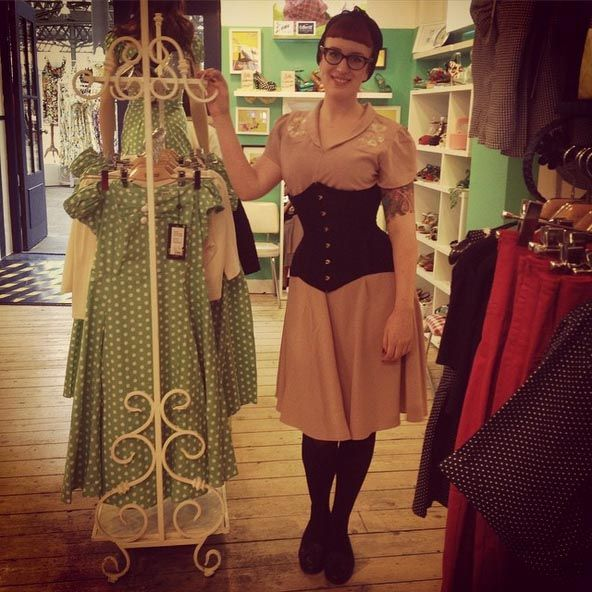 Elise, from our lingerie concession at Collectif, Spitalfields, London wears our Morticia Corset in black satin with a dress by Collectif.