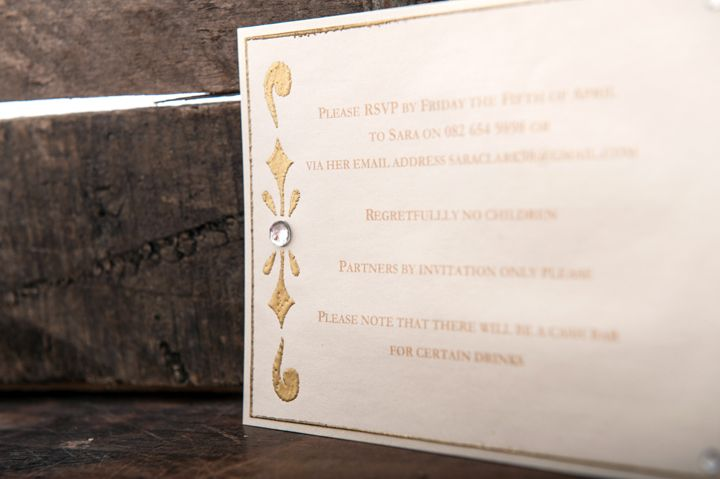 Invitation card with gold embossed design, gold edging and a large diamante.