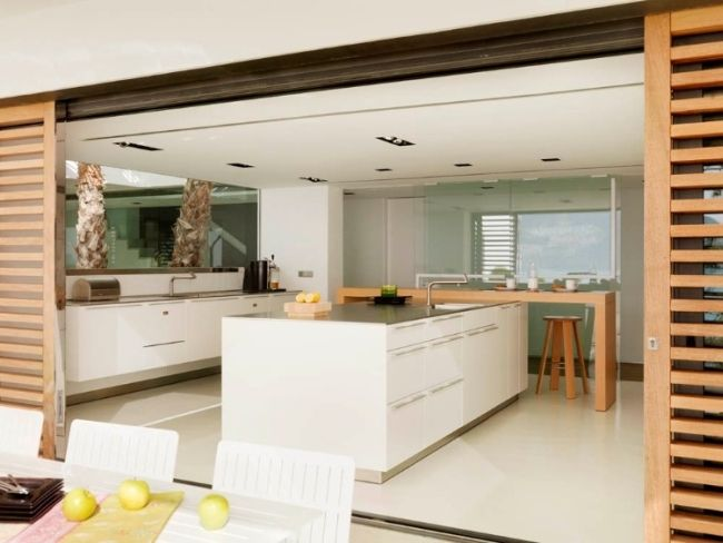 Nowoczesna kuchnia to kuchnia otwarta! Przesuwna, ażurowa ściana i kuchnia połączona z tarasem. Kuchnia w nowoczesnym domu na wybrzeżu Hiszpanii to kuchnia w kolorach bieli i naturalnego, ciepłego drewna - zapraszam do obejrzenia inspiracji!
