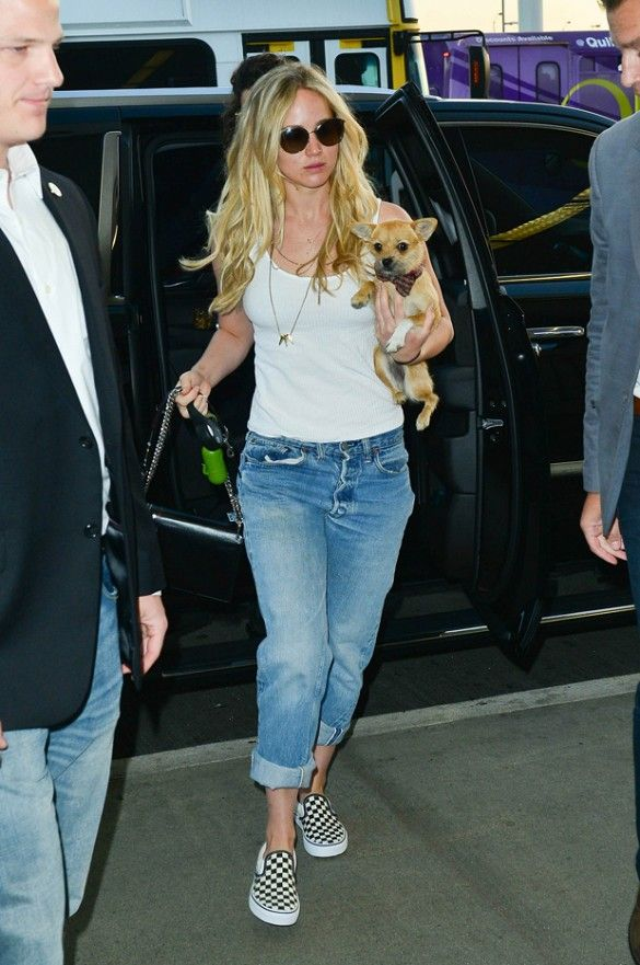 Jennifer Lawrence wears an easy white tank, boyfriend jeans, and checkerboard vans