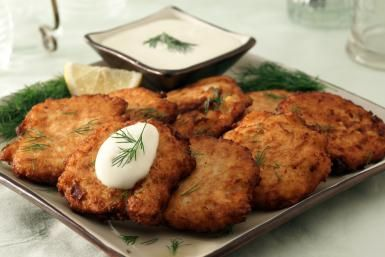 Latkes with garnishes and dressing - TheCrimsonMonkey / Getty Images