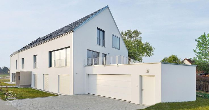 Baufritz Mehrfamilienhaus Schindele mit Satteldach und weißer Mineralputzfassade, anthrazitgraue Dachplatten, große Garage mit Extra Eingangstüre