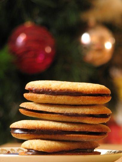 A Miláno cookie   Hozzávalók: 60g tönkölybúza liszt 60g teljes kiőrlésű liszt 60g liszt (finom) 1 tk sütőpor ½ tk só 100g vaj (szobahőmérsékletű) 110g porcukor 66g tojásfehérje (kb 2 nagy) 1 ek vanília kivonat 50ml friss narancslé A krémhez: 60ml tejszín 170g étcsoki 1 narancs reszelt héja
