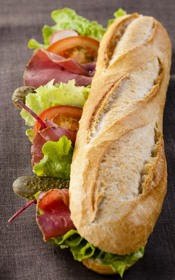 Sandwich L'Ambigu : tranches de pastrami, sauce mayonnaise à la moutarde en grains, tomate, salade verte, oignons frits et cornichon à la russe