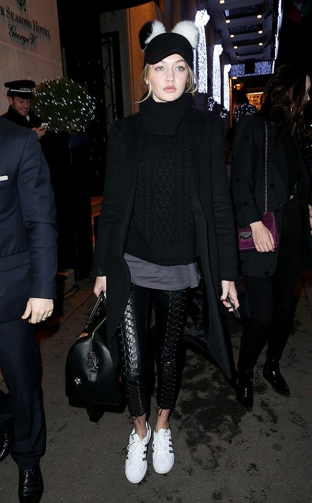 Gigi Hadid wears a cable-knit turtleneck, gray t-shirt, long black coat, lace-up leggings, Adidas sneakers, a baseball hat with pom-pom detailing, and a leather satchel