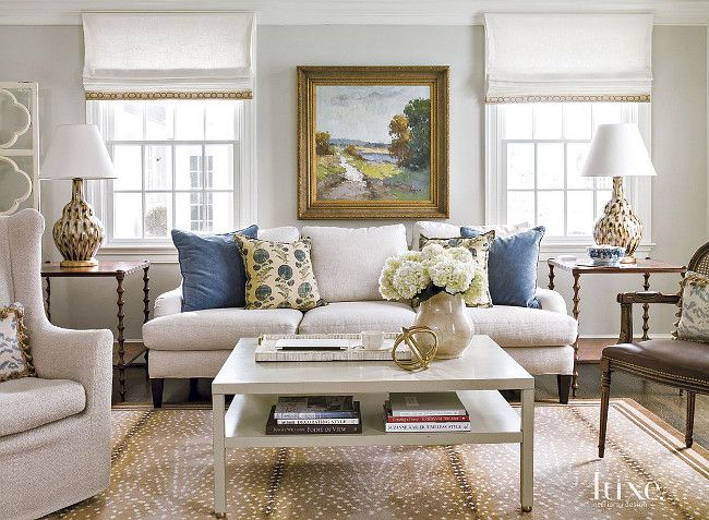 Manuel Canovas Pillows. Blue pillow fabric by Manuel Canovas adds pops of color to the family room's neutral Lee Industries sofa in Wesley Flax; pheasant feather lamps by Bunny Williams Home perk up a pair of Theodore Alexander side tables. Beth Gularson. Helen Norman Photography