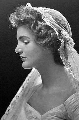 """Jackie wore a """"demure pearl choker, her grandmother's lace veil, a tiara of orange blossoms and a gown stitched from fifty yards of cream faille. Holding fast to bridal tradition of wearing something borrowed and something blue, she clutched her mother's lace handkerchief and wore a blue garter"""