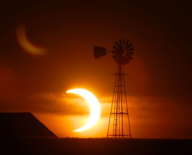 The sun sets behind a barn and windmill on Sunday, May 20, 2012, southwest of Ellis, Kansas - Solar Eclipse Courtesy: Steven Hausler/The Hays Daily News via AP