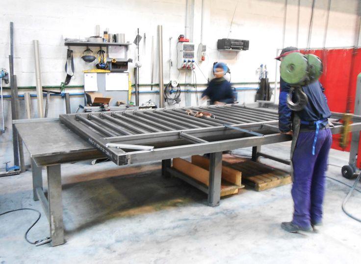 Herreros trabajando en la fabricación de una puerta metálica