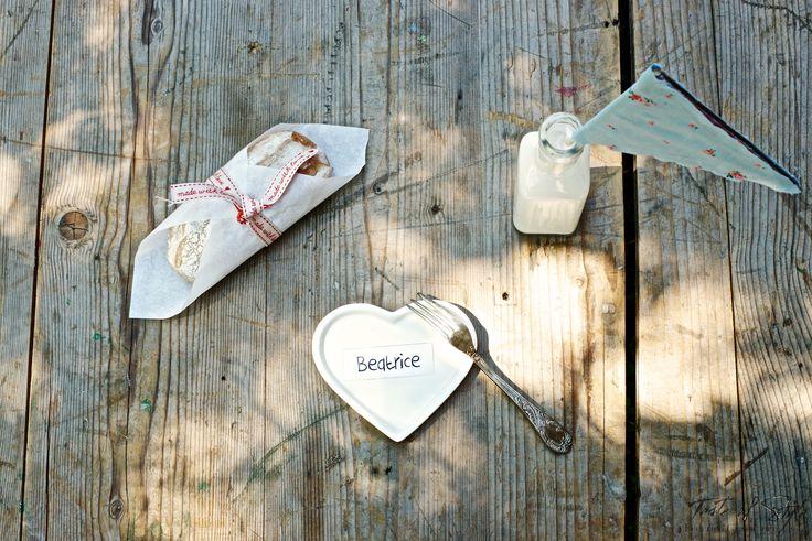 Una colazione sbarazzina con un piattino a forma di cuore (Tintacorda www.tintacorda.it) una bottiglietta di latte con una bandierina handmade e un panino francese avvolta nella velina. Una colazione al volo e via.