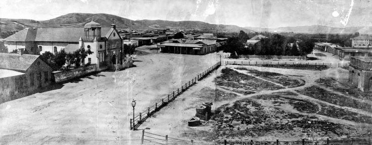 1869 - View of Calle Principal (now Main Street) looking northwest with the Old Plaza Church seen on the left. To the right is the Los Angeles Plaza (square at the time) with two gas lamps, one on each of its corners. These were the first gas lamps installed in the City of Los Angeles.