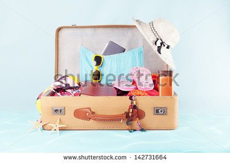 retro suitcase with full of clothes,books and passport on blue background - stock photo