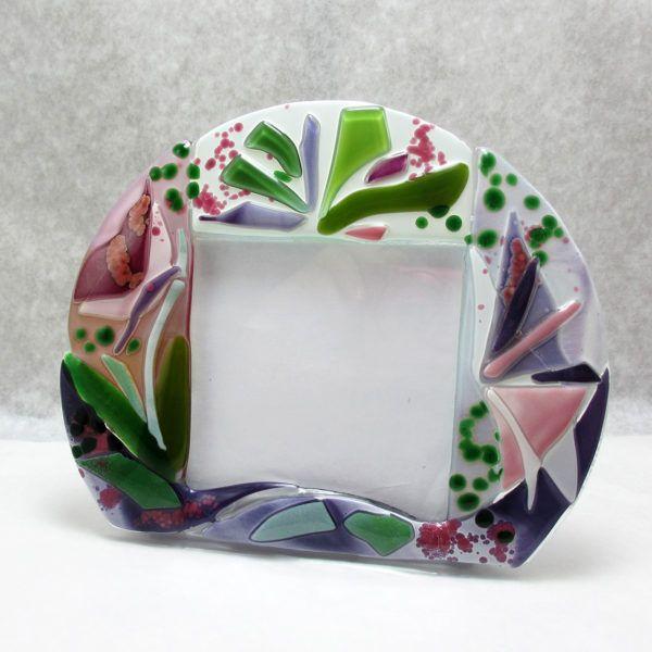 """Portafoto """"Spring"""" (PT07)è una cornice a tutto tondo dal fondo bianco. La base bianco opale dà maggiore risalto ai colori vivaci e festosi della primavera. Un tripudio di colori rosa, violetti e di verdi danzano festosi."""