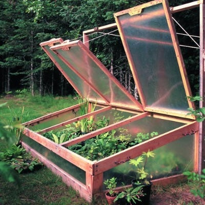Alaskan-style coldframe built with pressure-treated 2-by-4s and fiberglass sheeting. Pulley-drawn cords make it easier to open for ventilation.