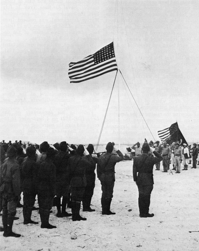 TO THE COLORS sounds as the American flag is raised over Wake Island for the first time since December 1941.